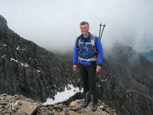 Standing-on-the-summit-edge-of-Ben-Nevis-north-face-with-Tower-Ridge-in-the-background