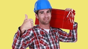 Handyman carrying tool box on shoulder and giving the go-ahead